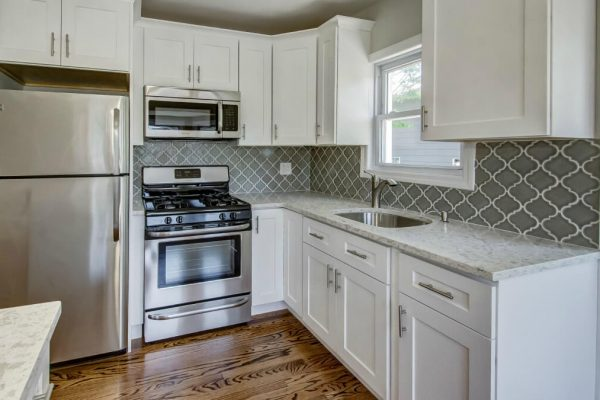 kitchen remodel with quartz counters, custom cabinets, Moroccan backsplash, wood flooring and stainless steel appliances